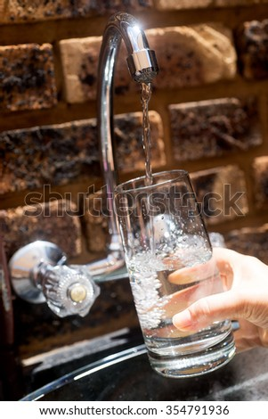 Water pouring into a glass from the tap - stock photo