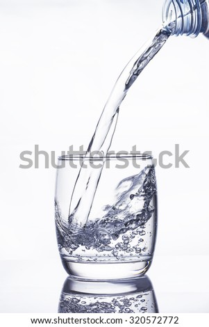 Water pouring into the glass on white background - stock photo