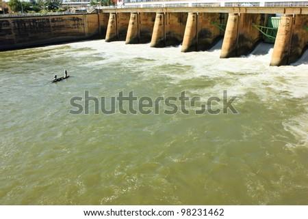 Water pouring through the sleus gates at dam - stock photo