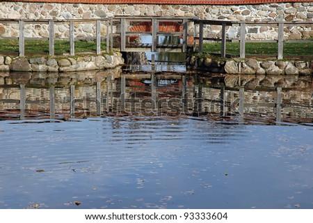 Water pouring through the small dam gates. Luke manor in Estonia - stock photo