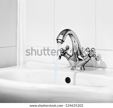 Water pours out of the open valve - stock photo