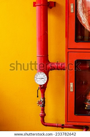 Water pressure gauge of the fire extinguisher with red water pipe on wall - stock photo