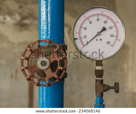 Water pressure meter installed on a blue pipe - stock photo