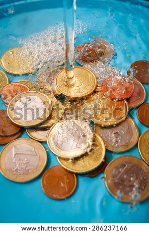 Water price concept with euro currency coins and water drops, vertical studio shot - stock photo