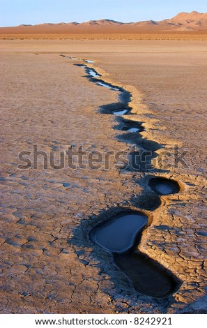 water puddles drying up on lakebed - stock photo