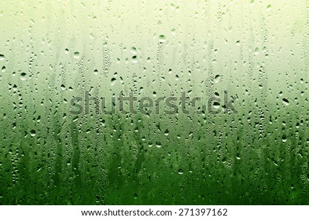 Water Rain Drop on the Green Glass in The Night Raining Season for Texture Background - stock photo
