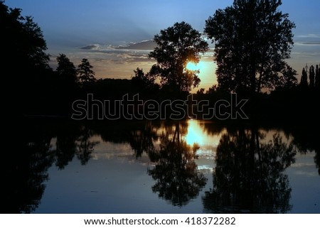 Water reflection in the bayou on dead arm of the river Elbe in Czech republic. Blue and golden colors. - stock photo