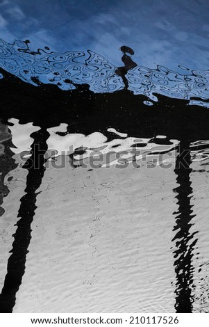 water reflection of a girl standing on the bridge - stock photo