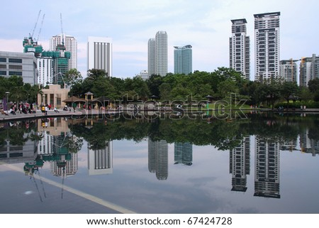Water reflection of Kuala Lumpur City Center and a park