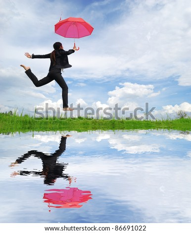 Water reflection,Red umbrella woman jump to sky - stock photo