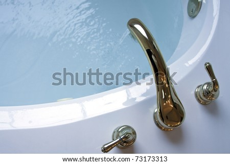water running from gold plated faucet flowing into a garden tub - stock photo