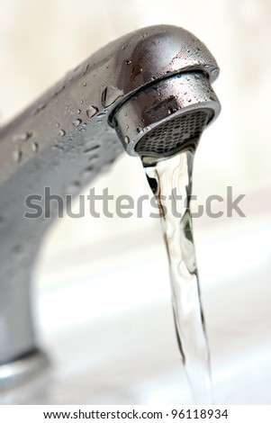 Water running from tap. Macro, shallow depth of field - stock photo