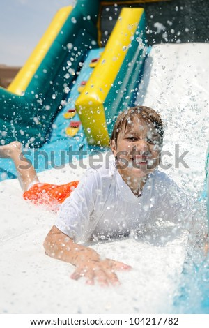 Water Slide Splashdown. Young boy sliding down an inflatable water slide and making a splash. - stock photo