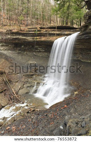 Water spills smoothly ofver a 50' overhang at Tinker Falls in Cortland County in New York State - stock photo