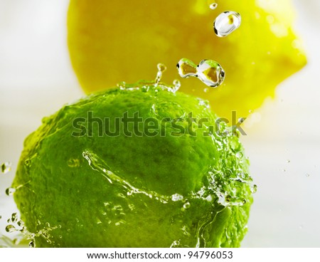 Water splash above yellow lemon and green lime. - stock photo