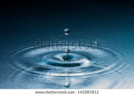Water splash in dark blue color with a drop of water - stock photo