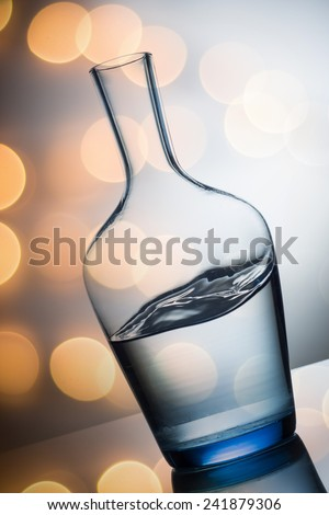 water splash in glass on colorfull light background close up - stock photo
