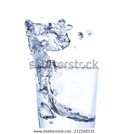 Water splash into glass on white background - stock photo