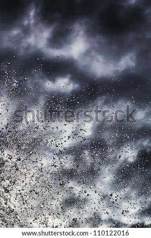 Water splashed against the backdrop of a stormy sky - stock photo