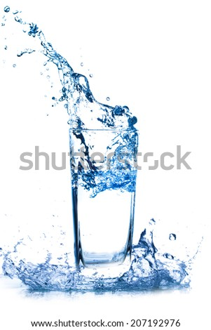 Water splashes out of the glass on a white background.