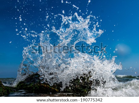 Water splashing. Crystal clear sea water beating against the rocks and cliffs. Blue sky above the beach in the sun zenith refreshing drops of ocean water. Sea waves break on the shore after a storm - stock photo