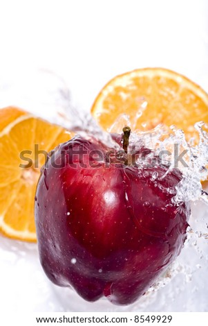 Water splashing down on an apple and orange - stock photo