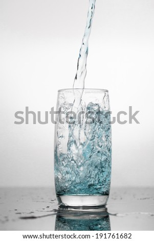 Water splashing in a glass, isolated on white