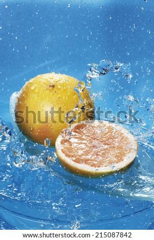 Water splashing on fresh grapefruits - stock photo