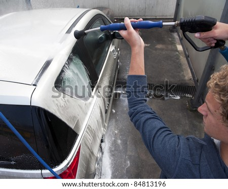 Water spray gun, held by a man, used to wash a car with soap - stock photo