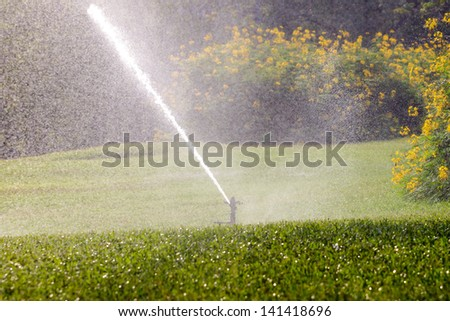 Water springer turning and watering the green grass - stock photo