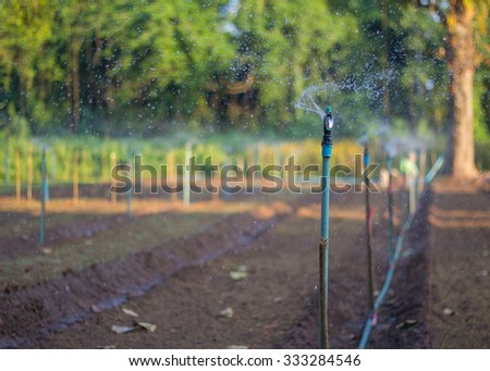 Water sprinkler irrigation of agricultural field. - stock photo