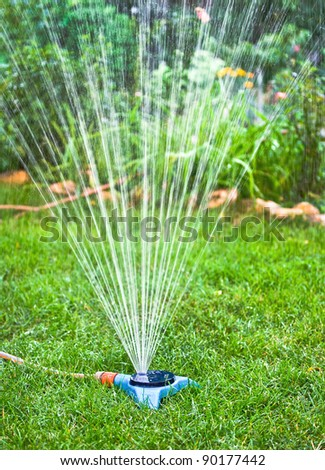Water sprinkler. Irrigation system - technique of watering in the garden. Lawn sprinkler spraying water over green grass. - stock photo