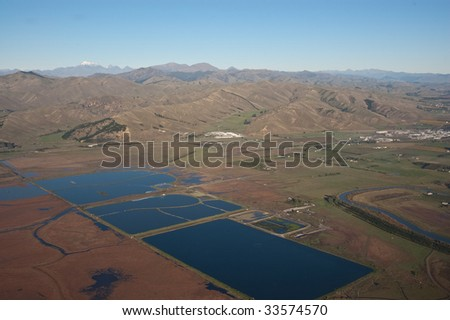Water storage ponds on the outskirts of Blenheim with mountains in the background - stock photo