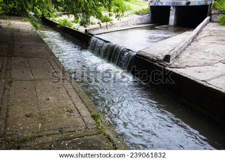 Water stream flowing out the underground tunnel into the Lybid river in Kyiv. - stock photo
