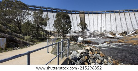 Water streaming and overflowing  over the  massive concrete wall and slipway  of Wellington Dam near Collie Western Australia on a  fine morning in spring after heavy rainfall upstream.