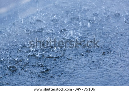 Water surface with rain drops falling - stock photo