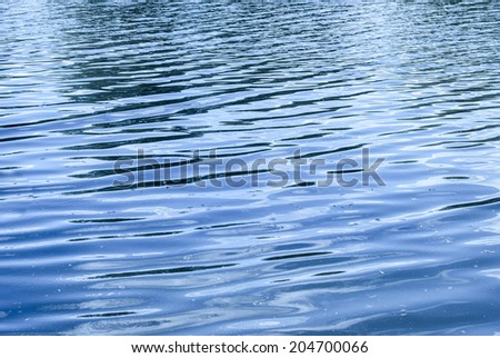 water surface with ripples and reflection of landscape - stock photo