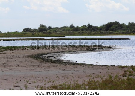 Water surface with small sand island, blue sky in background