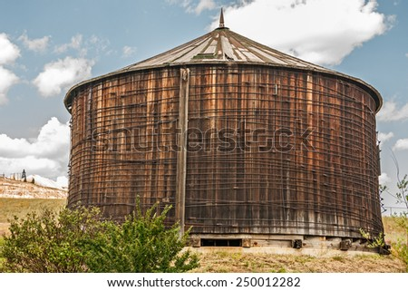 Water tank constructed of clear redwood lumber with a conical roof system. - stock photo