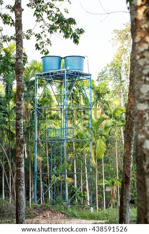 Water tanks are installed on an elevated platform. Water from nearby source is pumped upward to the tanks. It flows downward through pipe system to palms, rubber trees and others that a farmer plants. - stock photo