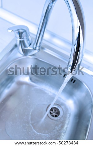 Water tap and sink in a modern kitchen. - stock photo