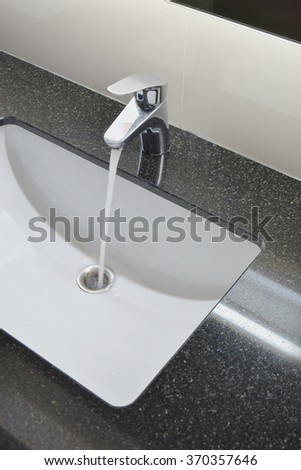 Water tap and under counter wash basin with black granite top - stock photo