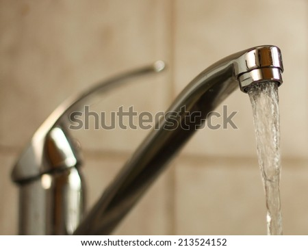 Water tap with flowing water. Selective focus, shallow depth of field.