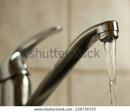 Water tap with flowing water. Selective focus, shallow depth of field. - stock photo