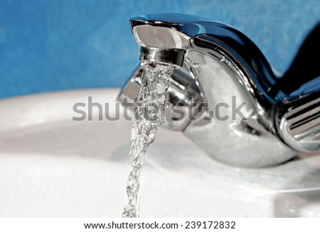 Water tap with flowing water. Selective focus, shallow depth of field (DOF).  - stock photo