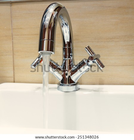 water tap with modern design in bathroom - stock photo