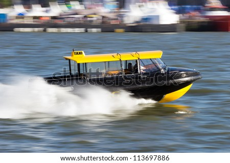 Water taxi speeding over the Meiuse river in Rotterdam, The Netherlands