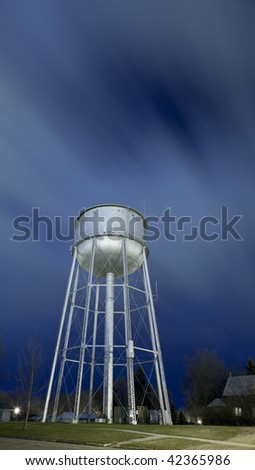 water tower at night with streaking clouds above