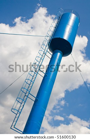 Water tower on blue and clouby sky background - stock photo