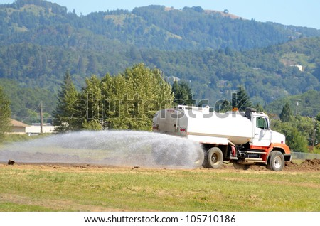 Water truck wetting down a road at the  removal  a rock hill at a airport expansion project in Oregon - stock photo